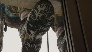 En snöröjares sko utanför ett fönster
