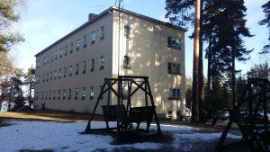 Trägungor på en snöig gräsmatta framför en ljusgul stenbyggnad i tre våningar, Esperi Hoitokoti Rehabia.