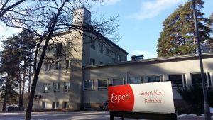 En rödvit skylt med texten Esperi Koti Rehabia framför en rappad beige byggnad med en hög skorsten.