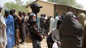 Långa köer övervakas av soldater utanför en vallokal i Kazaure i Nigeria.