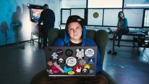 Hakkeri Benjamin Särkkä istuu tietokoneella ja hymyilee.