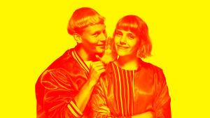 AIKUISET-sarjan näyttelijä Arttu kuiskaa Oonan korvaan. Molemmat hymyilevät keltaisessa kuvassa.