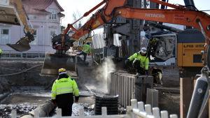 En grävmaskin arbetar och några byggnadsarbetare övervakar.