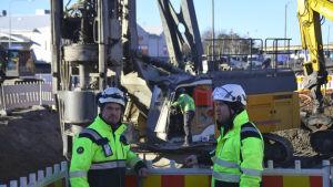 Två män med hjälmar på huvudet står vi byggplatsen.
