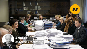 Personer sitter vid ett långt bord. En text med orden analys och Magnus Hertzberg finns på bilden.