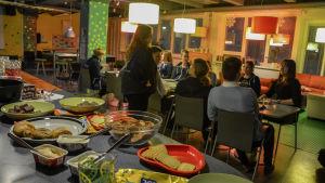 Unga samlade till fest kring ett bord.