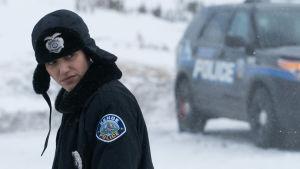 Den lokala polisen Kim (Emmy Rossum) sneglar skeptiskt under sin polismössa.