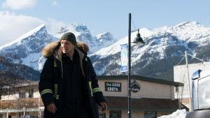 Niels spanar ut över trakten med de höga bergen i bakgrunden.
