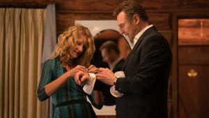 Grace (Laura Dern) hjälper maken Niels (LIam Neeson) med manchetterna.