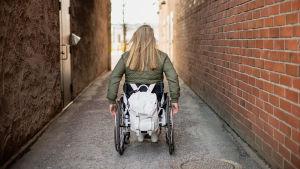 Nette Kiviranta pyörätuolissa selkä kameraan päin pienellä kujalla tiilirakennusten välissä. Pyörätuolin selkänojalla roikkuu valkoinen reppu.