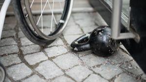 Pyörätuolin rengas ja kahvakuula pitämässä ovea auki.