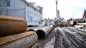 Flera pålar ligger på rad nära bygget.