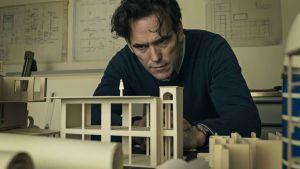 Jack sitter lutad över en miniatyrmodell av en byggnad.
