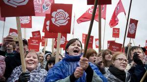 Unga kvinnor håller plakat med danska Socialdemokraternas logo medan de lyssnar på ett tal.