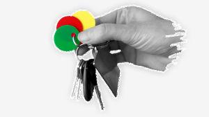 Kuvassa on käsi, joka pitelee avainnippua, jossa on avainten lisäksi kolme eriväristä pyöreää lätkää.