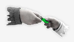 Kuvassa kaksi kättä. Opettajan käsi ojentaa oppilaalle vihreän lätkän hyvästä käytöksestä.