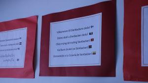 En papperslapp med texten välkommen till Stenbackens skola på många olika språk är upphängd på en vit vägg.
