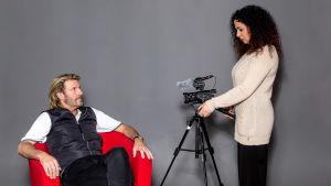 promobild från dokumentären Anders jag och hans 23 andra kvinnor där Anders sitter i röd fåtölj och tittar upp mot Nahid Persson till höger som står med en videokamera på stativ.