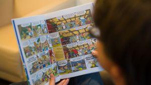 Henkilö lukee Asterix-sarjakuvaa