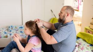 Aleksei letittää tyttärensä hiuksia.