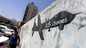 Jemeniter i huvudstaden Sanaa passerar en väggmålning som föreställer en amerikansk drönare. Bilden tagen i april 2017.