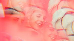 Tuure Boeliuksen hymyilevät kasvot kaleidoskooppimaisesti pinkin taustan edessä.
