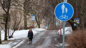 Kvinna går längs med gångled i förortsmiljö.