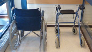 Rullstol och rullator i ett vindskåp.
