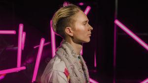 Vaaleahiuksinen mies seisoo sivuttain vaaleanpunaisten neonvalotankojen edessä ilmeettömänä.