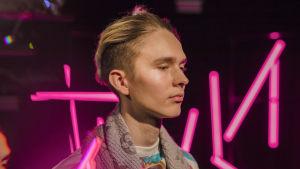 Vaaleahiuksinen nuori mies katsoo alaviistoon vaaleanpunaisten neontankojen edessä, kuva rajattu hartioista alaspäin.