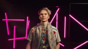 Vaaleahiuksinen nuori mies katsoo kameraan pinkkien neonvalotolppien edessä seisten, kuva rajattu vyötäröstä alaspäin.