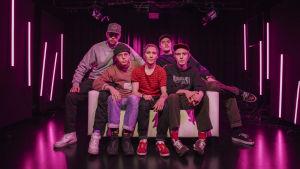 Aarnikotkat-yhtye istumassa sohvalla. Kuvassa MC Pösö, Carlito, Santana, Rumilus ja Leo G.