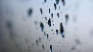 Vattendroppar på slät, grå, vertikal yta.
