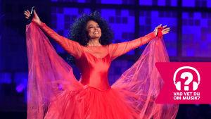 Diana Ross ler brett med utsträckta armar.