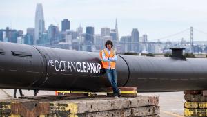 Hollantilainen Boyan Slat seisoo rannalla meriä puhdistavan keksintönsä kanssa.