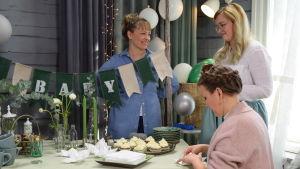 Tre kvinnor som dukar upp ett festbord. På bordet finns ett fat med muffins, vikta servetter, stearinljus och vita blommor i udda vaser.