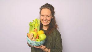 Tara Lange pitelee vihanneksia ja hedelmiä sisältävää astiaa käsissään.