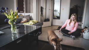 Hunden Lucky och Stefanie leker på vardagsrummets golv.