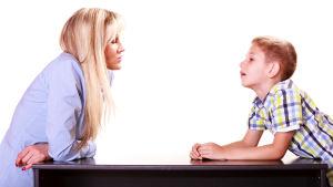 mamma och son diskuterar vid bord