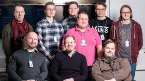 Nio leende män, tre sittande sex stående
