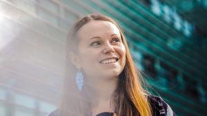 Punertavahiuksinen nainen katsoo hymyillen oikealle yläviistoon, kuva rajattu hartioista alaspäin.