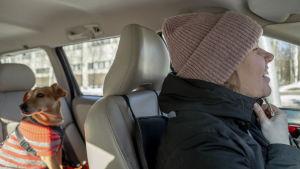 Stefanie kör bil och ler medan hunden Lucky sitter i baksätet.
