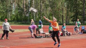 Nainen heittää urheilukentällä liitosaapasta, taustalla ihmisiä katsomassa.
