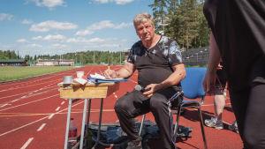 Mies istuu ulkona urheilukentällä pulpetti edessään ja mikrofoni ja kynä kädessään.