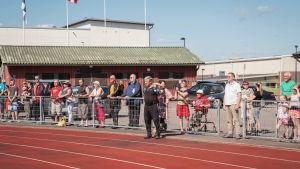 Eri-ikäisiä ihmisiä seisoo kesällä urheilukentän reunalla jotain katsomassa.