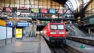 Ett rött tåg vid en perrong på stor tågstation.