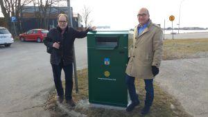 Två män poserar vid ett grönt smart sopkärl.