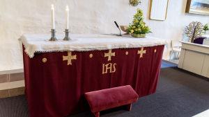 Två tända ljus vid altaret.