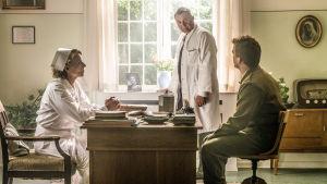 Ylihoitaja Margrethe Lund (Benedikte Hansen), ylilääkäri Bent Neergard (Jens Jørn Spottag) sekä vielä armeijan univormuun pukeutunut Erik Larsen (Morten Hee Andersen) ylihoitajan toimistossa sarjassa Sairaanhoito-opisto