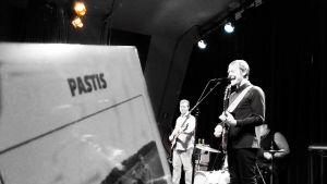 Bandet Pastis vinylskiva i förgrunden och sångaren Markus Nymalm i bakgrunden live på scen.